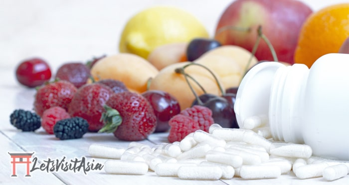 Multivitamins as immune support while traveling among some fruit in the background