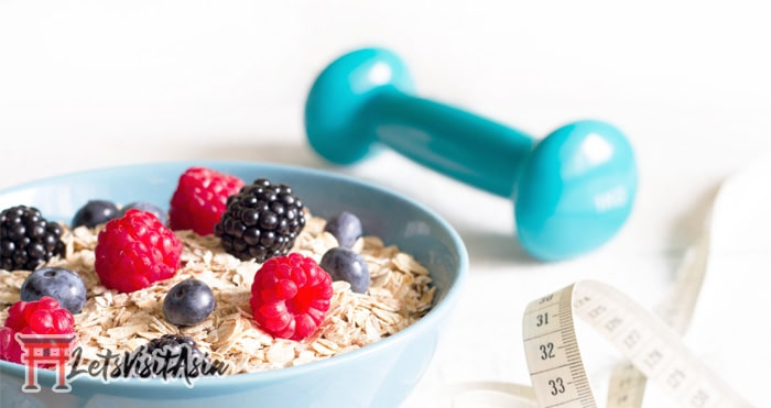 A bowl of oats with some berries on top with a dumbbell